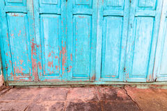 Vintage wooden blue cyan doors. Old house with vintage wooden blue cyan doors and gray cement floor. Vintage blue cyan doors concept use for background Stock Image