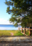 Vintage wooden board table in front of dreamy and abstract forest lake landscape with lens flare. Royalty Free Stock Photo