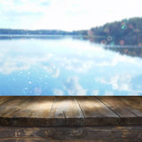 Vintage wooden board table in front of dreamy and abstract forest lake Stock Photography
