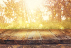 Vintage wooden board table in front of dreamy and abstract forest landscape with lens flare. Stock Image