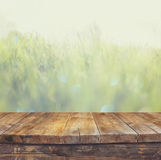 Vintage wooden board table in front of dreamy and abstract landscape with lens flare. Royalty Free Stock Images