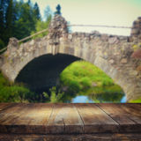 Vintage wooden board table in front of old bridge view at the park Royalty Free Stock Photography