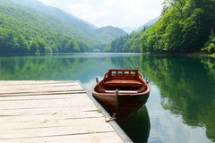 Vintage wooden boat. At pier on mountain lake. Biograd lake, Montenegro Royalty Free Stock Images