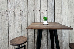 Vintage wooden cafe table with a green flower on top Royalty Free Stock Photo