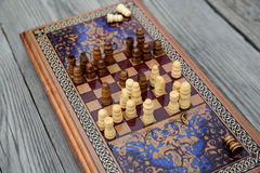 Vintage wooden chess on a board. Vintage wooden chess on a wooden chess board. Black and white pieces on the board Royalty Free Stock Image