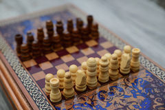 Vintage wooden chess on a board. Vintage wooden chess on a wooden chess board. Black and white pieces on the board Stock Photo