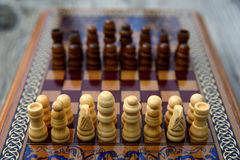Vintage wooden chess on a board. Vintage wooden chess on a wooden chess board. Black and white pieces on the board Royalty Free Stock Images