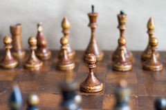 Vintage wooden chess pieces on an old chessboard. Royalty Free Stock Image