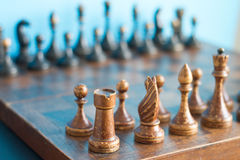 Vintage wooden chess pieces on an old chessboard. Royalty Free Stock Photos