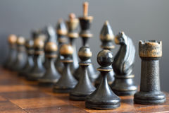 Vintage wooden chess pieces on an old chessboard. Royalty Free Stock Images