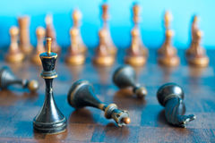 Vintage wooden chess pieces on an old chessboard. Stock Photos