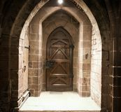 Vintage wooden door. Closed in sandstone wall in cathedral Royalty Free Stock Photo