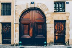 Vintage wooden door with framed door panels and round windows protected by ornate metal lattices. Shiny brass door royalty free stock photo