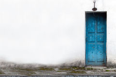 Vintage Wooden Door in White Wall. A blue vintage wooden door in white wall Royalty Free Stock Image