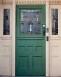 Vintage wooden entrance door with stained glass. An old fashioned entrance door with stained glass panels Stock Image