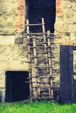 Vintage wooden ladder. Wood, bricks and stone royalty free stock images
