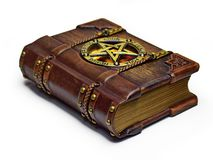 Vintage wooden - leather Grimoire book with a pentagram and Latin names of Classical elements. On the front cover plate. The book is captured from the left side royalty free stock photography