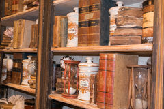 Vintage wooden library with Antique Consumed Books, Ceramic Cont. Ainers and Hourglass Stock Images