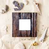 Vintage wooden photo frame on craft paper with sand and sea shells mock up Stock Photography