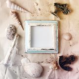 Vintage wooden photo frame on craft paper with sand and sea shells mock up Stock Image