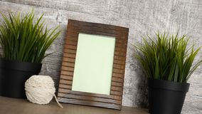 Vintage wooden photo frame. Next to two pots of grass stock footage