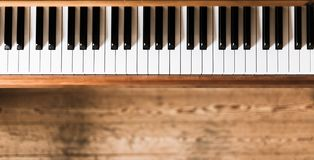 Vintage wooden piano keys, wooden blurry floor. Vintage wooden piano. Keys in the foreground, wooden floor in the blurry background instrument rustic jazz royalty free stock photo