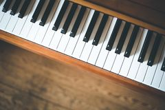 Vintage wooden piano. Keys in the foreground, wooden floor with text space in the blurry background. Vintage wooden piano keys with text space instrument rustic stock images