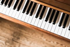 Vintage wooden piano. Keys in the foreground, wooden floor with text space in the blurry background. Vintage wooden piano keys with text space instrument rustic royalty free stock photos