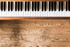 Vintage wooden piano. Keys in the foreground, wooden floor with text space in the blurry background. Vintage wooden piano keys with text space instrument rustic stock photography