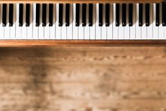 Vintage wooden piano. Keys in the foreground, wooden floor with text space in the blurry background. Vintage wooden piano keys with text space instrument rustic royalty free stock photo