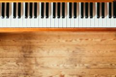 Vintage wooden piano. Keys in the foreground, wooden floor with text space in the blurry background. Vintage wooden piano keys with text space instrument rustic royalty free stock photography