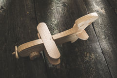 Vintage wooden plane on wooden board. Sunshine through the window Royalty Free Stock Images