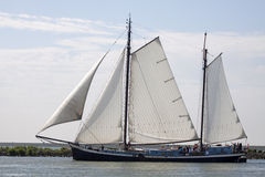 Vintage wooden sailboat. ENKHUIZEN, THE NETHERLANDS - JULY 18,2015: Vintage traditional wooden sailing ship under sail leaving the port of enkhuizen with sunny Royalty Free Stock Photos