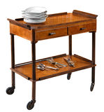 Vintage wooden serving trolley on wheels. Vintage rectangular wooden serving trolley with a top gallery, two drawers and lower shelf on wheels with a stack of Stock Photos