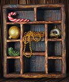 Vintage wooden shadow box with candy canes, christmas tree toy and golden watch. Christmas composition on vintage shadow box with candy canes, christmas tree toy Royalty Free Stock Photo