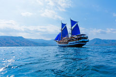 Vintage Wooden Ship with Blue Sails Stock Images