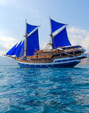 Vintage Wooden Ship with Blue Sails Royalty Free Stock Photos