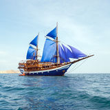 Vintage Wooden Ship with Blue Sails Stock Photography