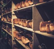 Vintage wooden shoe lasts in a row on the old shelves. Royalty Free Stock Photography