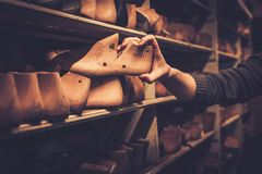 Vintage wooden shoe lasts in a row on the old shelves. Stock Photo