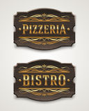 Vintage wooden signs for pizzeria and bistro. With golden lettering and decorative elements Royalty Free Stock Photo