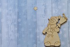 Cheerful snowman with broom and bird and Christmas star on light background with stylized snowflakes. stock image