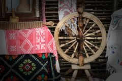 Vintage wooden spinning wheel and household items. Royalty Free Stock Photography