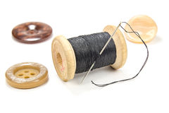 Vintage wooden spool of black thread, needle and buttons on white background Stock Photography
