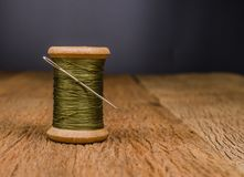 Retro wooden spool thread with needle sewing. Vintage wooden spool thread with needle sewing on wooden board Stock Images