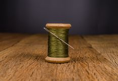 Retro wooden spool thread with needle. Vintage wooden spool thread with needle on wooden board Stock Photography