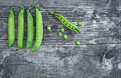 Vintage wooden surface with located pods of green peas. Vintage wooden surface for design with beautifully located pods of green peas stock photography