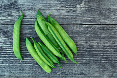 Vintage wooden surface with located pods of green peas stock photos