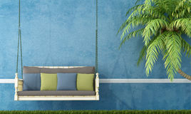 Vintage wooden swing against blue wall Royalty Free Stock Photos