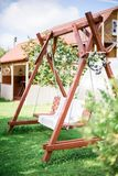 Vintage wooden swing in the garden near house Royalty Free Stock Photo